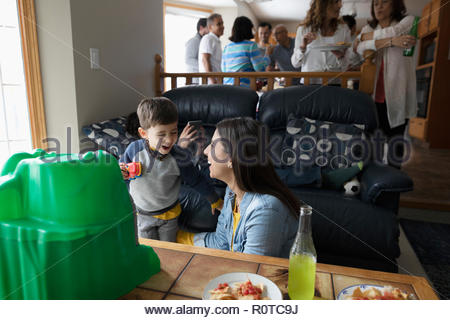 Latinx mother and toddler son playing in living room - Stock Photo