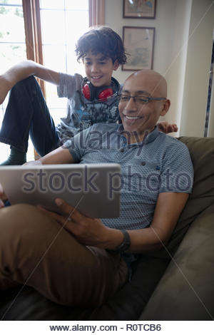 Latinx father and son using digital tablet - Stock Photo