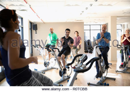 Class clapping for instructor leading spin class in gym - Stock Photo