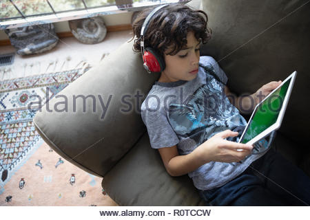 Latinx boy with headphones using digital tablet on sofa - Stock Photo