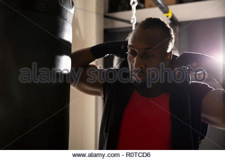 Male boxer at punching bag in gym - Stock Photo