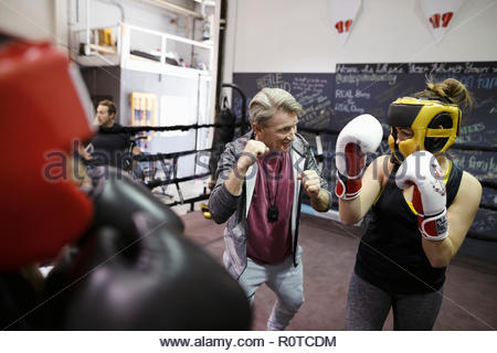 Trainer guiding female boxer training in boxing ring in gym - Stock Photo