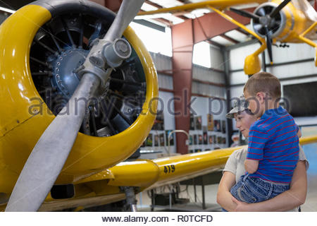Female army pilot mother showing son airplane in military airplane museum - Stock Photo