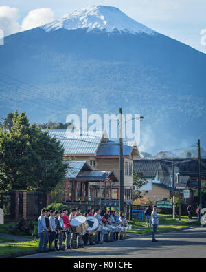 kids rehearsing its fanfare at the street in front of vulcan hornopiren with snowy peak at background at Hornopiren city, Chile, Patagonia - Stock Photo