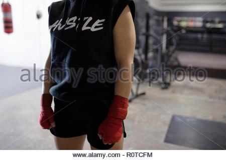 Tough female boxer in gym - Stock Photo
