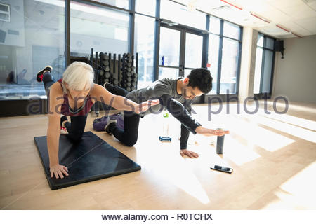 Personal trainer guiding senior woman doing balance stretch in gym studio - Stock Photo