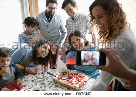 Man with camera phone photographing Latinx multi-generation family celebrating birthday with cake - Stock Photo