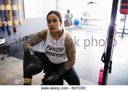 Portrait confident, tough female boxer resting in gym - Stock Photo