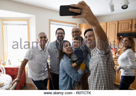 Latinx multi-generation family taking selfie with camera phone in kitchen - Stock Photo