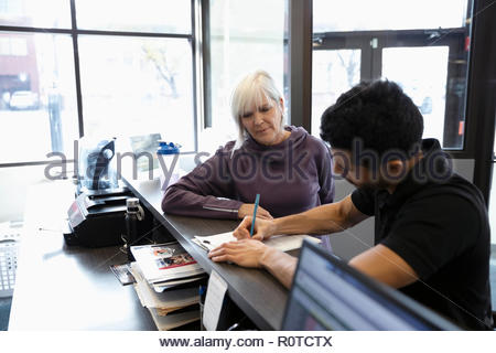 Personal trainer meeting with senior woman in gym - Stock Photo