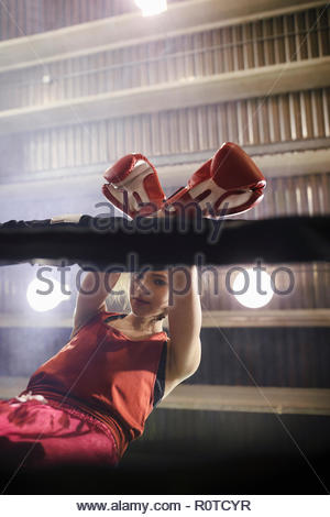 Tough female boxer in boxing ring - Stock Photo