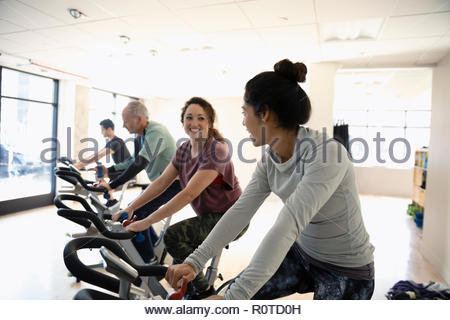 Smiling women riding exercise bikes in spin class in gym - Stock Photo