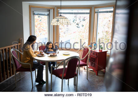 Mother watching son using digital tablet at kitchen table - Stock Photo