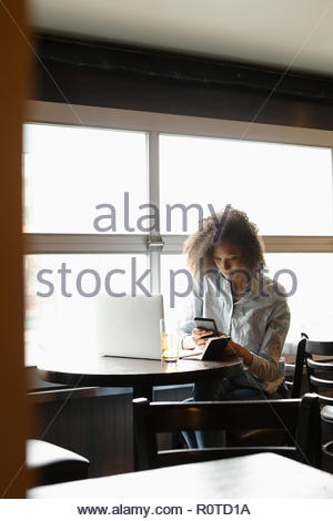 Woman using smart phone at laptop in bar - Stock Photo