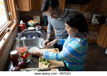 Man watching senior mother cooking in kitchen - Stock Photo