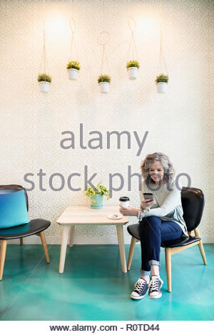 Senior woman drinking coffee and using smart phone in cafe - Stock Photo