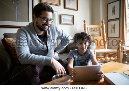 Latinx father and son using digital tablet in living room - Stock Photo