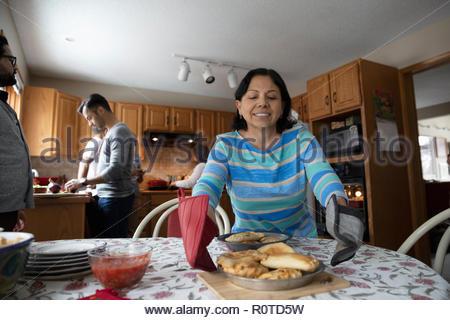 Latinx senior woman placing food on table - Stock Photo