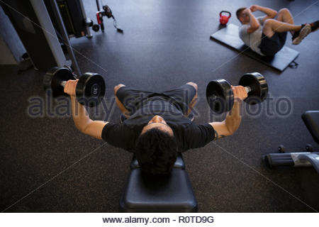 Man exercising, doing chest press exercises with dumbbells in gym - Stock Photo