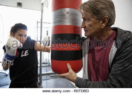 Trainer holding punching bag for female boxer training in gym - Stock Photo
