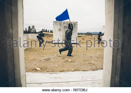 Man with blue flag paintballing in field - Stock Photo