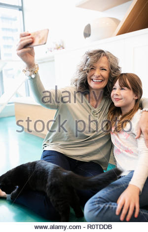 Happy grandmother and granddaughter with cat taking selfie in cat cafe - Stock Photo