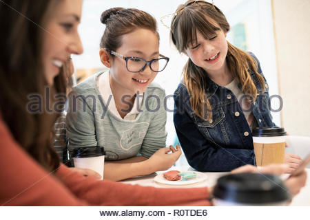 Mother and daughter with friend drinking coffee in cafe - Stock Photo