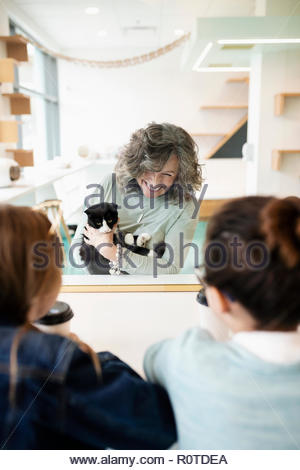 Smiling woman showing cat to girls in cat cafe - Stock Photo