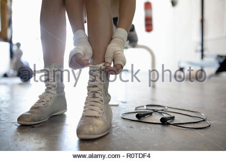 Close up female boxer tying shoes in gym - Stock Photo