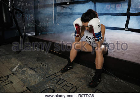 Tired female boxer resting in gym - Stock Photo