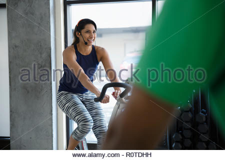 Instructor on exercise bike leading spin class in gym - Stock Photo