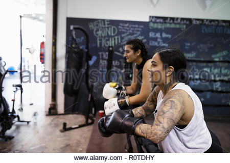 Female boxer with tattoos resting in gym - Stock Photo