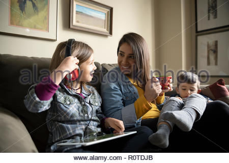 Latinx mom with children using digital tablets on sofa - Stock Photo
