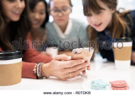 Mothers and daughters using smart phone and drinking coffee in cafe - Stock Photo