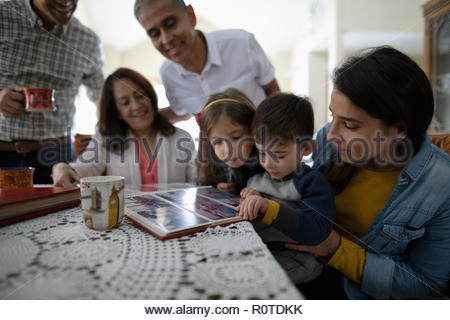 Latinx multi-generation family looking at photo album - Stock Photo