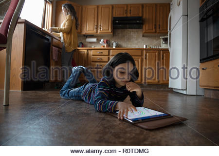 Boy using digital tablet on kitchen floor - Stock Photo