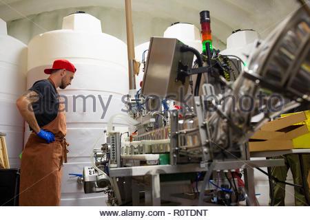 Man working in beer distillery - Stock Photo