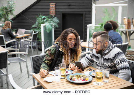 Couple with smart phone enjoying lunch on cafe patio - Stock Photo
