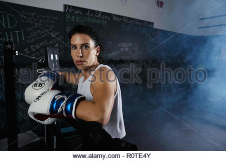 Portrait tough female boxer standing in boxing ring - Stock Photo