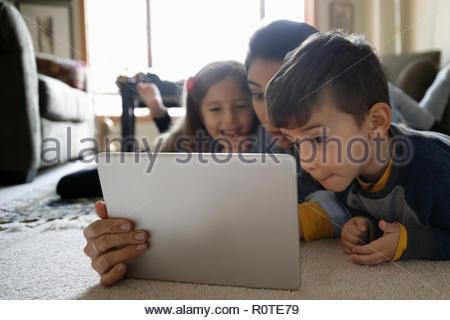 Latinx family using digital tablet on living room floor - Stock Photo