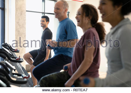 People riding exercise bikes in spin class in gym - Stock Photo