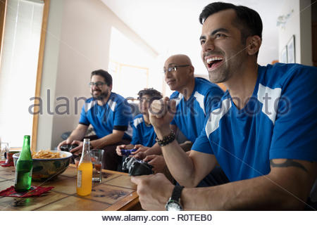 Enthusiastic Latinx multi-generation family playing sports video game - Stock Photo