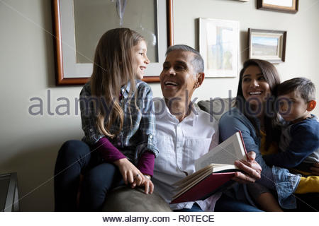 Latinx multi-generation family reading story on sofa - Stock Photo