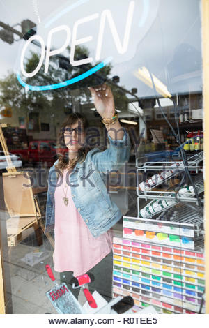 Female business owner turning on neon Open sign in art supply shop window - Stock Photo