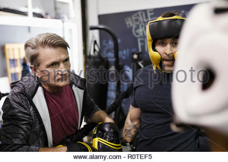 Male trainer and boxer training in gym - Stock Photo