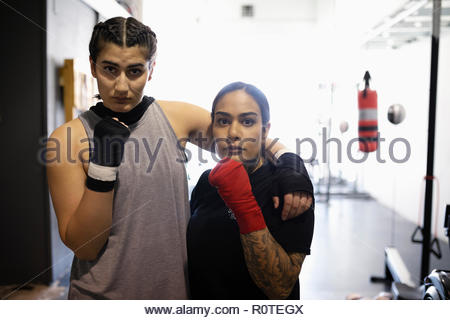 Portrait confident, tough female boxers in gym - Stock Photo