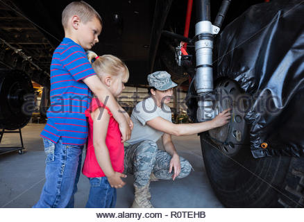 Female army engineer showing airplane landing gear to curious children - Stock Photo