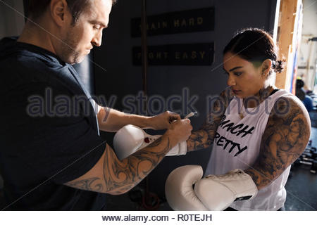 Trainer helping female boxer with boxing gloves in gym - Stock Photo