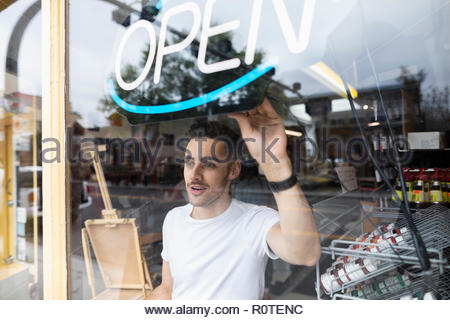 Male business owner turning on neon Open sign in shop window - Stock Photo
