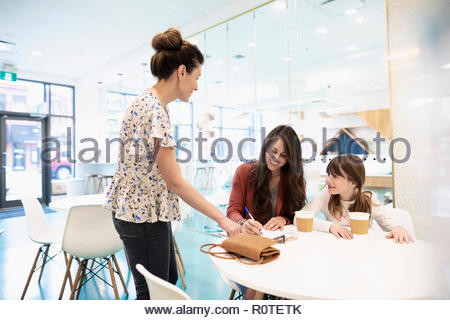 Mother and daughter drinking coffee and filling out adoption application in cat cafe - Stock Photo